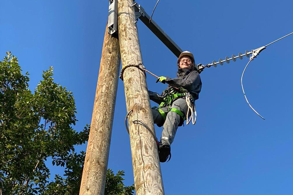 Junge Elektronikerin für Betriebstechnik klettert auf Strommast