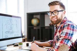 glücklicher junger Mann im karierten Hemd vor Computer