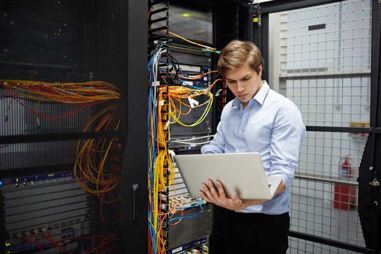 Junger Mann mit Labtop vor IT-Anlage