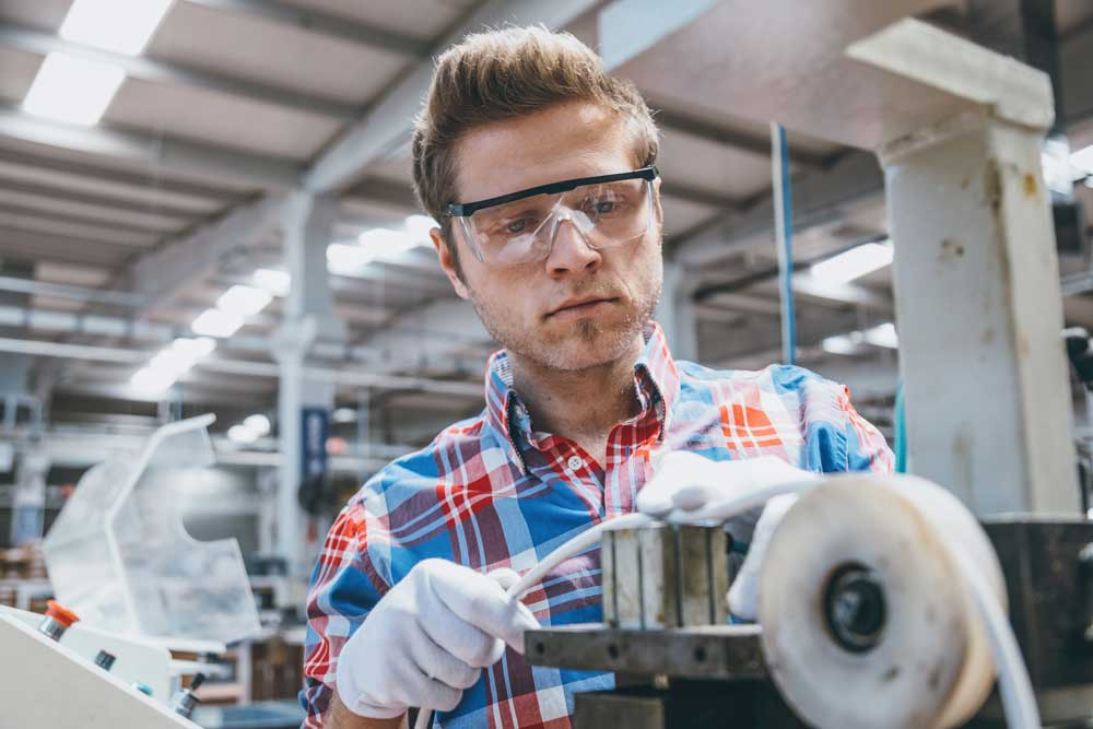 Junger Mann mit Schtzbrille und kariertem Hemd an Fertigungsanlage