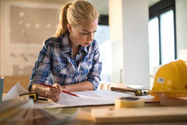 Blonde Frau sitzt am Tisch und schaut Baupläne an