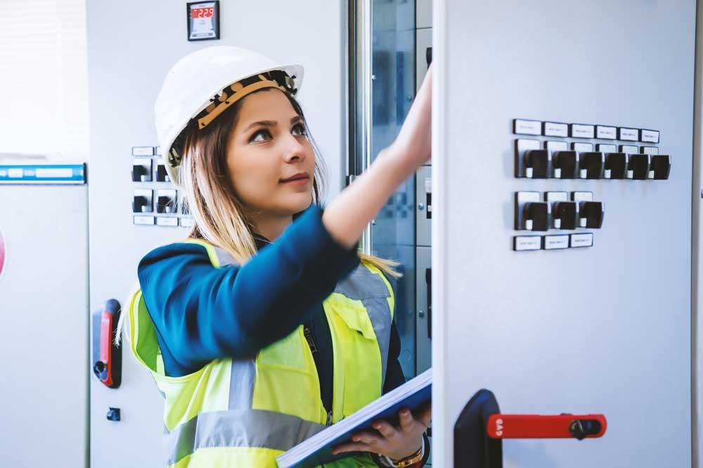 junge Frau mit weißem Helm im Energie-Kontrollraum