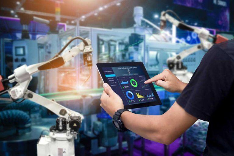 Hände mit Tablet vor modernen Roboteranlagen