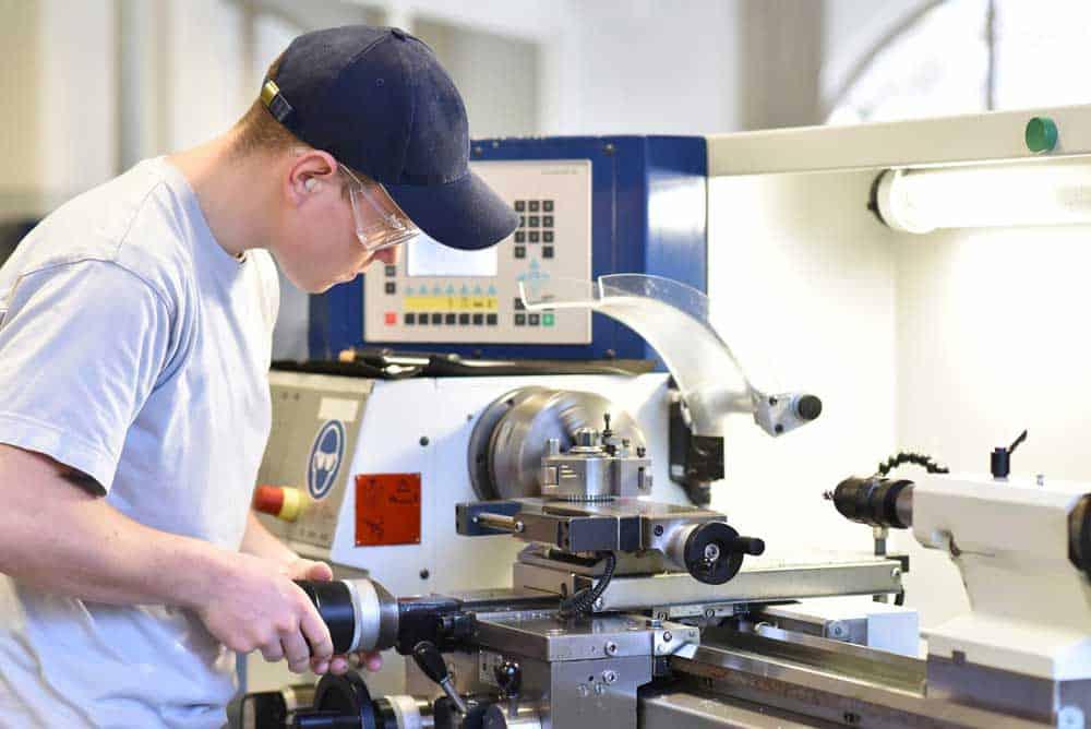Auszubildender mit blauer Kappe an Maschine
