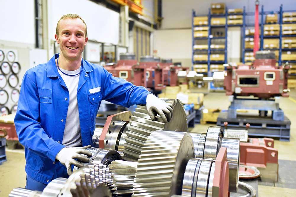 junger mann im Blaumann mit Maschinenteilen