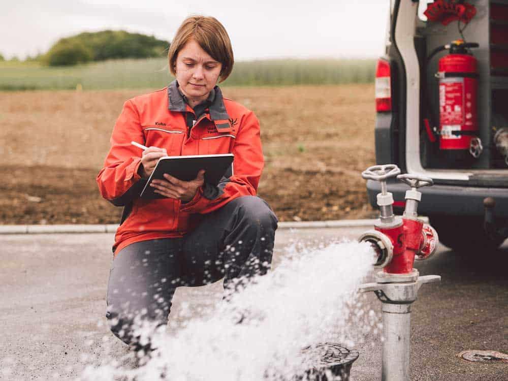 Junge Frau bei Spülung einer Trinkwasserleitung