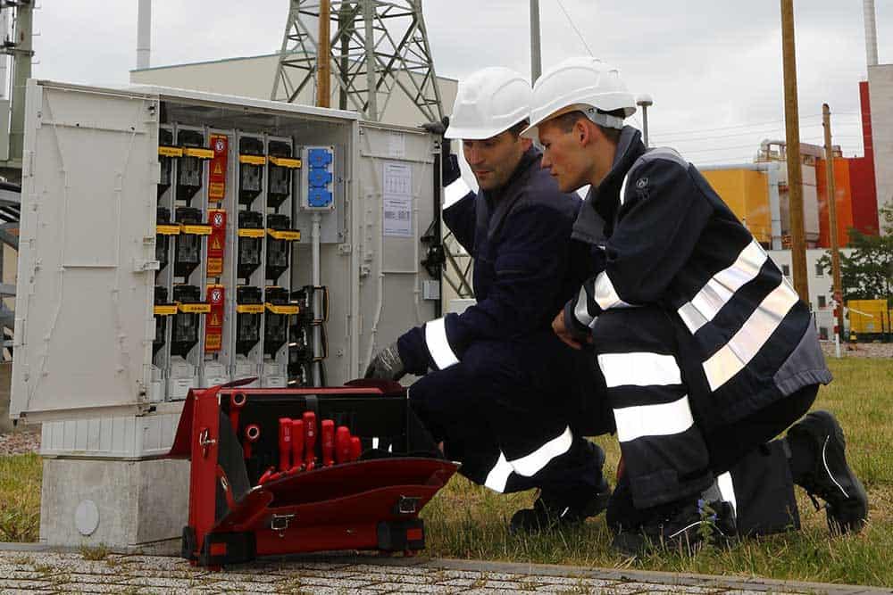zwei Techniker vor Stromkasten
