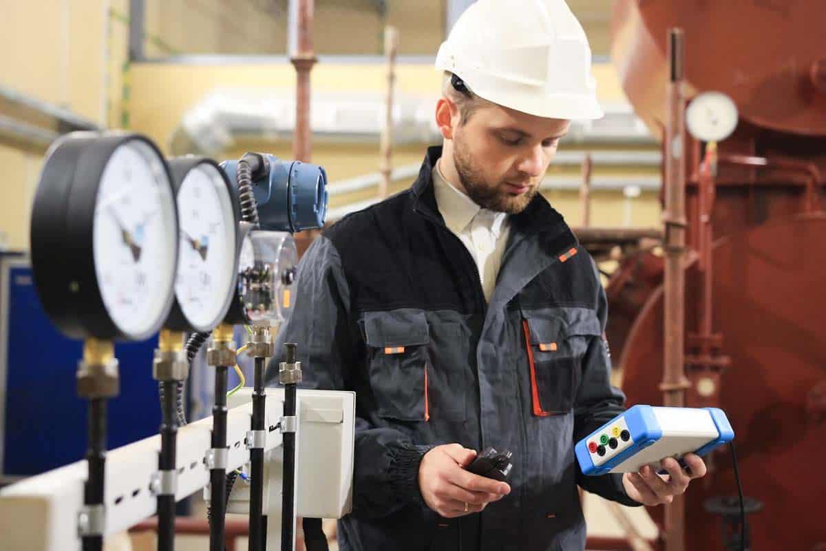 Ingenieur mit weißem Helm und Messgerät